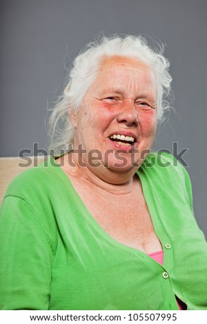 Happy relaxed senior woman with grey long hair sitting in chair. Studio shot isolated on grey background.