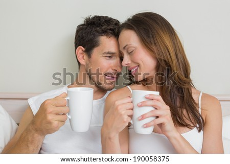Happy relaxed young couple with coffee cups at home - stock photo