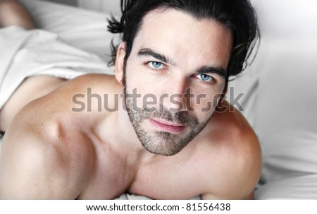 Happy relaxed young good looking man shirtless in bedroom - stock photo