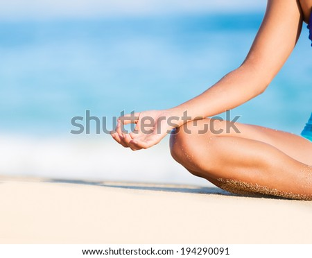 Happy relaxed young woman practicing yoga outdoors at the beach. Lotus position, Cloe up detail photo of hand. - stock photo