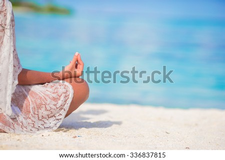 Happy relaxed young woman practicing yoga outdoors at white beach - stock photo