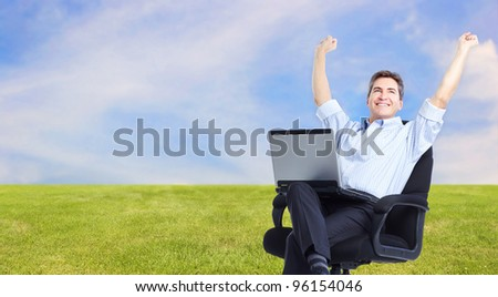 Happy relaxing businessman with laptop. Over blue sky. - stock photo