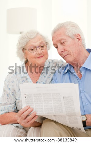 Happy relaxing senior couple reading newspaper together at home - stock photo