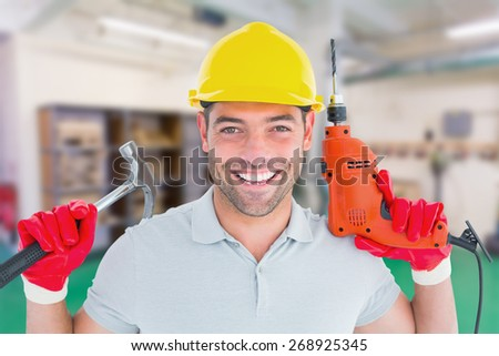 Happy repairman holding hammer and drill machine against workshop - stock photo