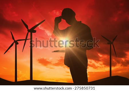 Happy repairman wearing hard hat while holding clipboard against sky and mountains - stock photo