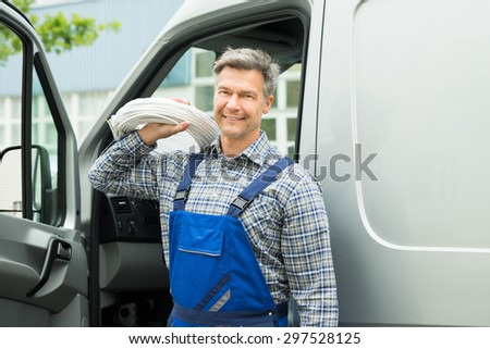 Happy Repairman With White Cable Coil Standing In Front Of Van - stock photo