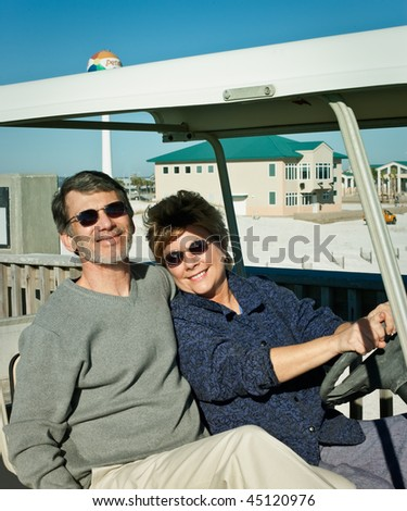 Happy retired couple having fun in an old golf cart at the beach. - stock photo