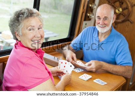 Happy retired couple playing cards in their motor home. - stock photo