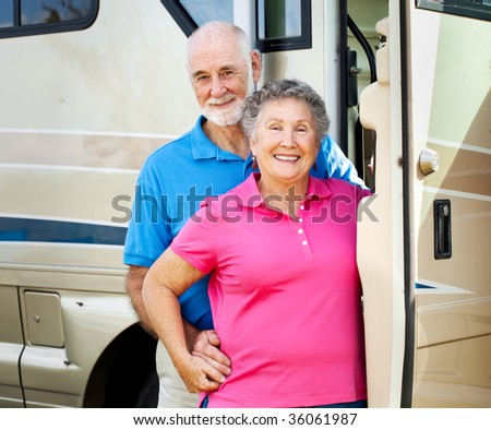 Happy retired couple posing in the doorway of their luxury motor home. - stock photo