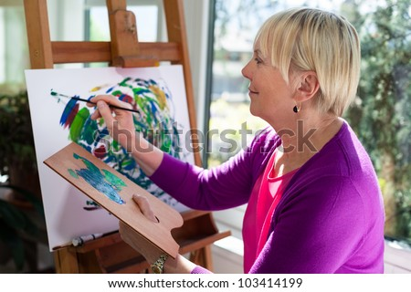 Happy retired woman painting on canvas for fun at home - stock photo