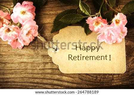 Happy Retirement message with small roses on rustic wooden table - stock photo