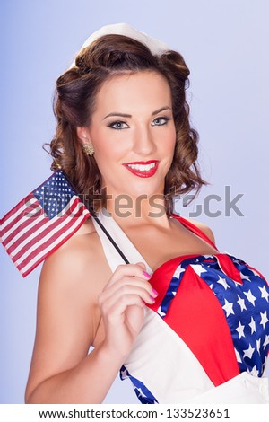 Happy retro pinup brunette in Old Glory outfit celebrates Independence Day waving American Flags - stock photo