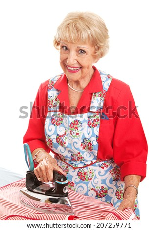 Happy retro senior lady ironing.  Isolated on white.