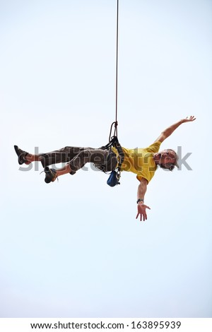 Happy rock climber hanging on rope - stock photo