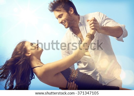 Happy romantic couple dancing open air under blue sky.
