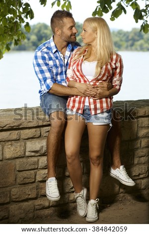 Happy romantic couple embracing at riverside, looking at each other, outdoor, full length, shorts, sport shoe. - stock photo