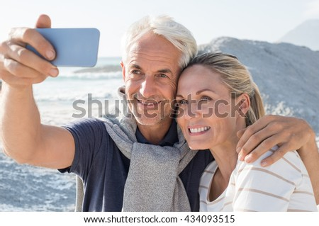 Happy romantic couple embracing on the beach and taking a photo with smart phone. Portrait of senior smiling couple taking a selfie in a summer vacation at sea. Happy mature couple take a picture. - stock photo