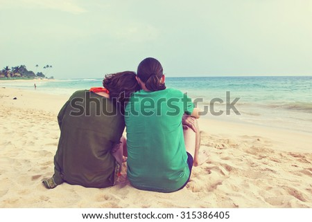 Happy romantic couple enjoying beautiful sunset on the beach. Vintage style toned image - stock photo