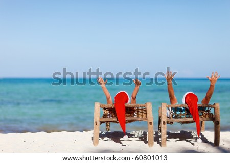 Happy romantic couple in red Santa hats at tropical beach relaxing on sun beds