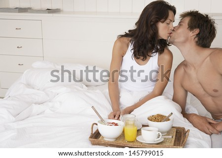 Happy romantic couple kissing by breakfast tray in bed - stock photo
