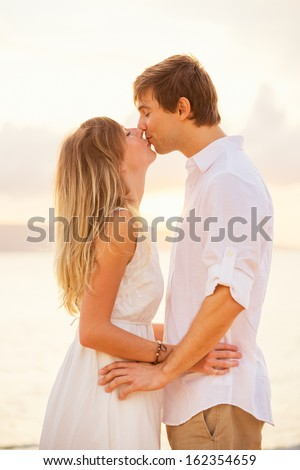 Happy romantic couple kissing on the beach at sunset, Man and woman in love  - stock photo