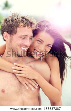 Happy romantic couple lovers on beach honeymoon having playful fun together during summer beach holidays. Cheerful young multiracial couple, Asian woman and Caucasian man in their twenties.