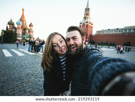 Happy romantic couple of tourists makes selfie self-portrait in front of Kremlin on the Red Square in Moscow while traveling across Russia - stock photo