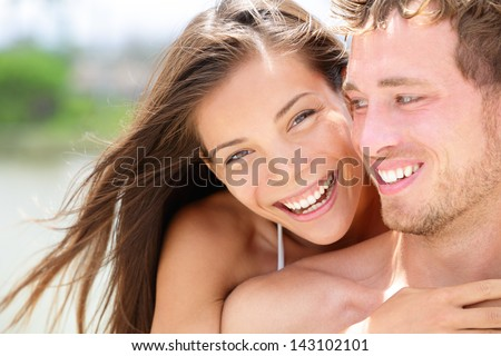 Happy romantic couple on beach in love. Portrait of joyful young multi-ethnic young couple embracing each other having fun outdoors during summer holidays vacation travel. Asian woman, Caucasian man. - stock photo