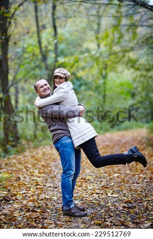 Happy romantic couple outdoor in the alley covered with fallen leaves - stock photo