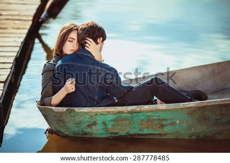 Happy romantic couple rowing a small boat on lake - stock photo