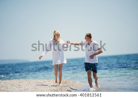 happy romantic couple running on the sea beach