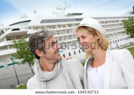 Happy romantic couple standing in front of cruise boat - stock photo