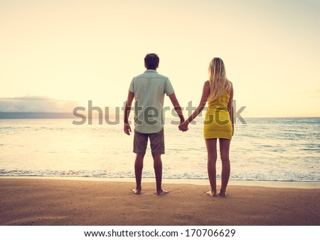 Happy Romantic Couple Watching the Sunset Holding Hands on Tropical Beach Vacation, Vintage Trendy Color Styling - stock photo