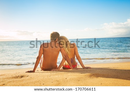 Happy Romantic Couple Watching the Sunset on Tropical Beach Vacation - stock photo
