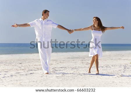 Happy romantic man and woman couple dancing and holding hands on a deserted tropical beach with bright clear blue sky - stock photo