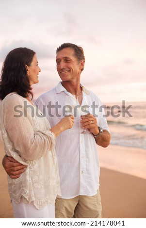 Happy Romantic Mature Couple Drinking Champagne on the Beach at Sunset.