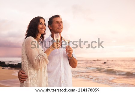 Happy Romantic Mature Couple Drinking Champagne on the Beach at Sunset. Vacation Travel Retirement Anniversary Celebration. - stock photo