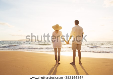 Happy Romantic Middle Aged Couple Enjoying Beautiful Sunset on the Beach. Travel Vacation Retirement Lifestyle Concept. - stock photo