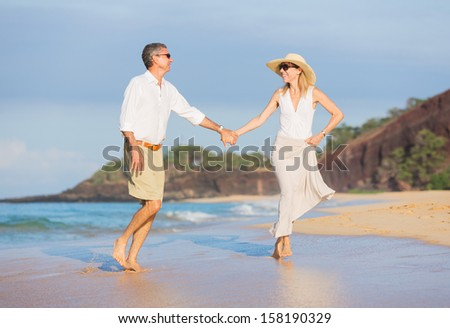 Happy Romantic Middle Aged Couple Enjoying Walk on the Beach, Vacation Retirement Concept - stock photo