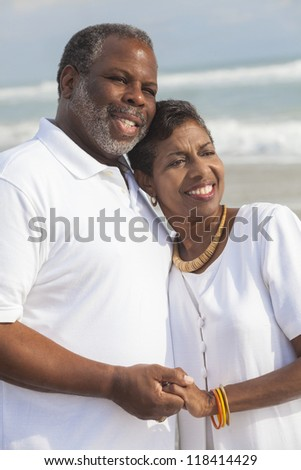Happy romantic senior African American man and woman couple holding hands on a deserted tropical beach - stock photo