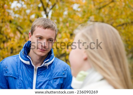 Happy romantic teen couple walking outdoors on cold autumn day - stock photo