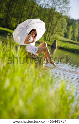 Happy romantic woman sitting by lake , holding parasol, wearing white dress