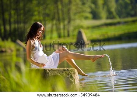 Happy romantic woman sitting by lake splashing water, wearing white dress - stock photo