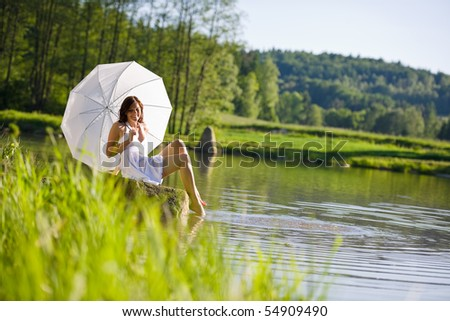 Happy romantic woman sitting by lake with parasol on sunny day