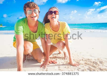 happy romantic young couple lying at a tropical beach - stock photo
