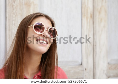 Happy romantic young woman in stylish round sunglasses with mirror lenses looking up with inspired joyful smile. Close up view of beautiful female with long hair daydreaming while posing indoors