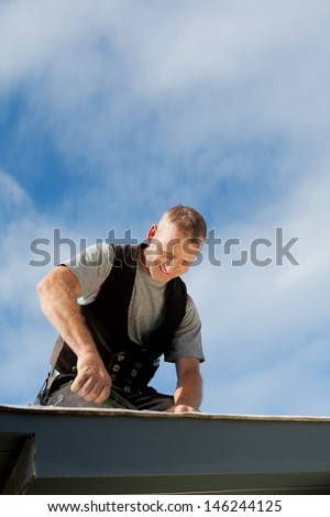 Happy roofer working on the rooftop under the sun - stock photo