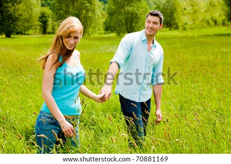 Happy running barefoot couple of two with trees in background smiling walk - stock photo