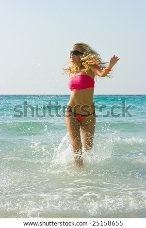 Happy running girl in the water