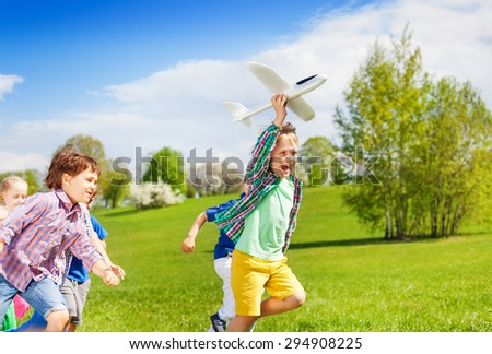 Happy running kids with white airplane toy - stock photo